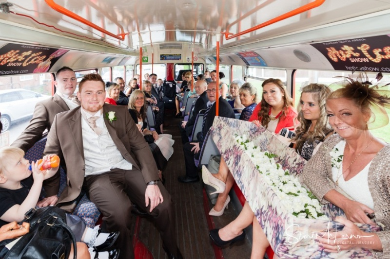 Wedding guests aboard a double-decker bus