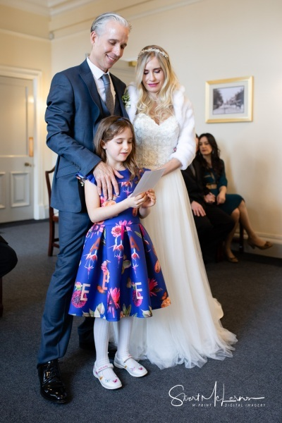 Newlyweds and daughter reading message at Stockport Town Hall