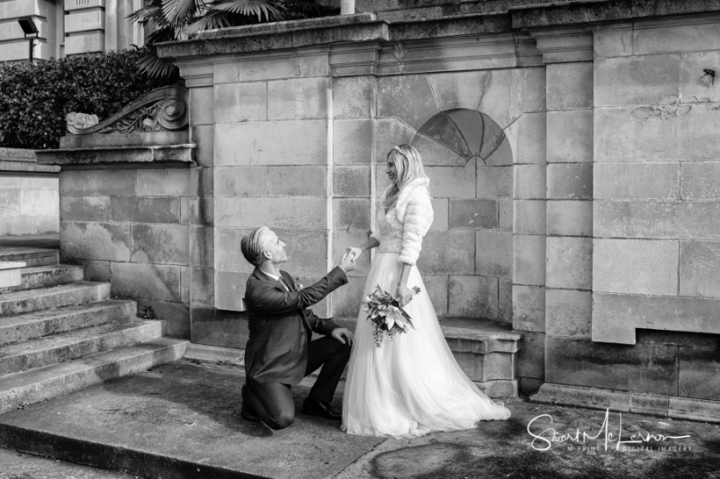 Groom on bended knee at Stockport Town Hall
