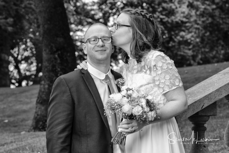 Bride kissing Groom's head at Dukinfield Park