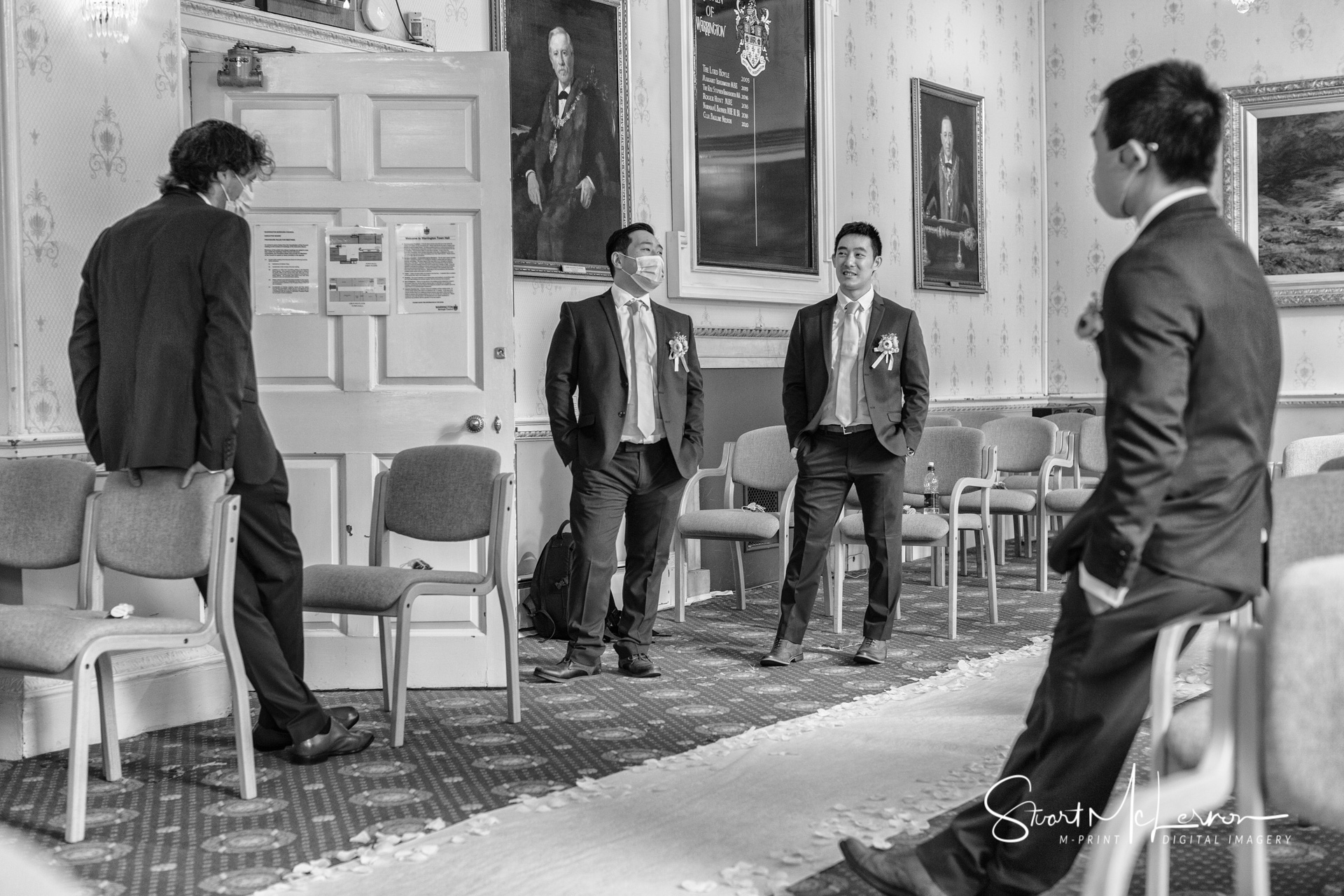 The groom and his groomsmen are socially distanced before the wedding ceremony at Warrington Town Hall
