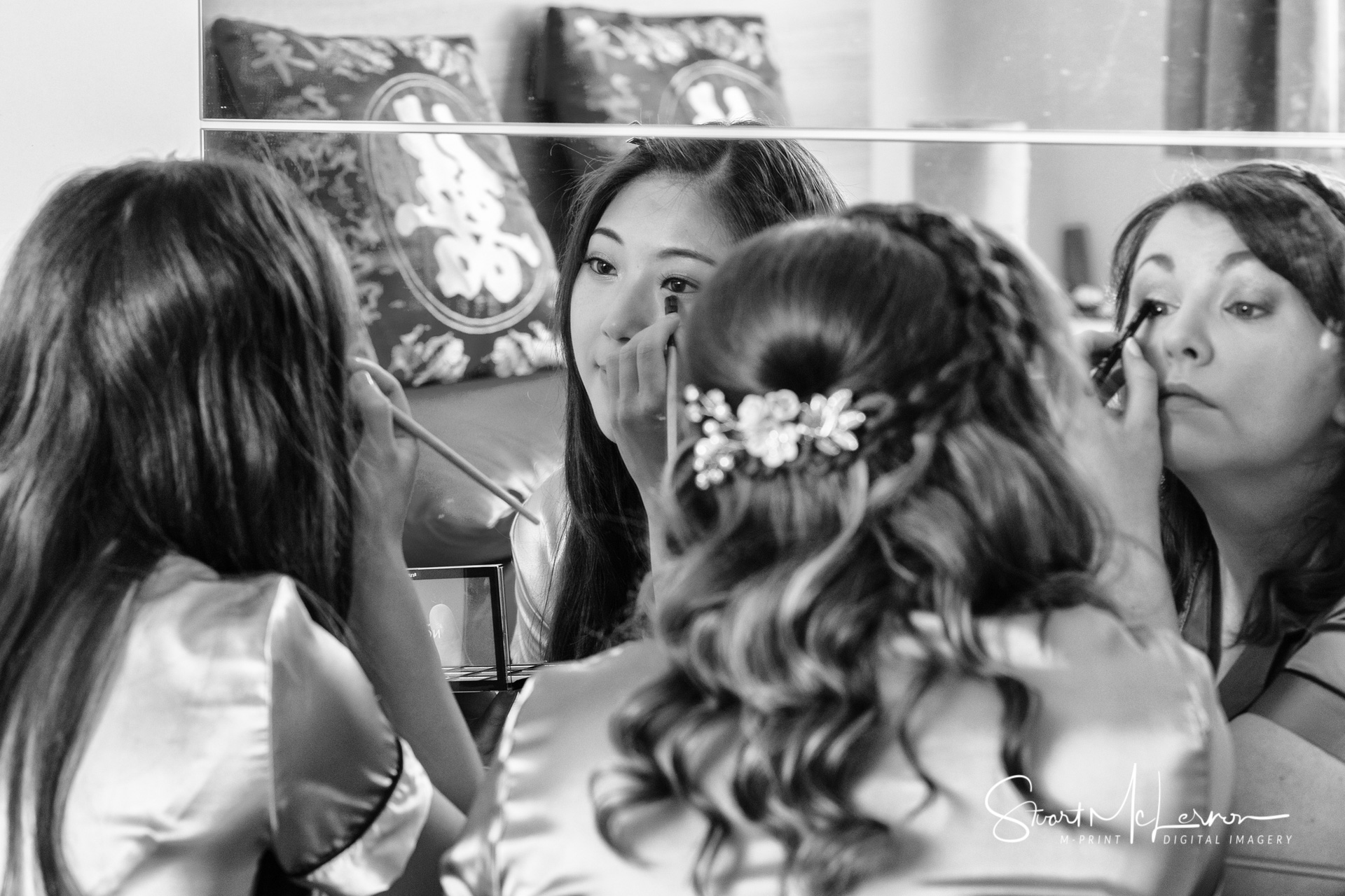 The bride and her bridesmaid share a bedroom mirror as they apply makeup