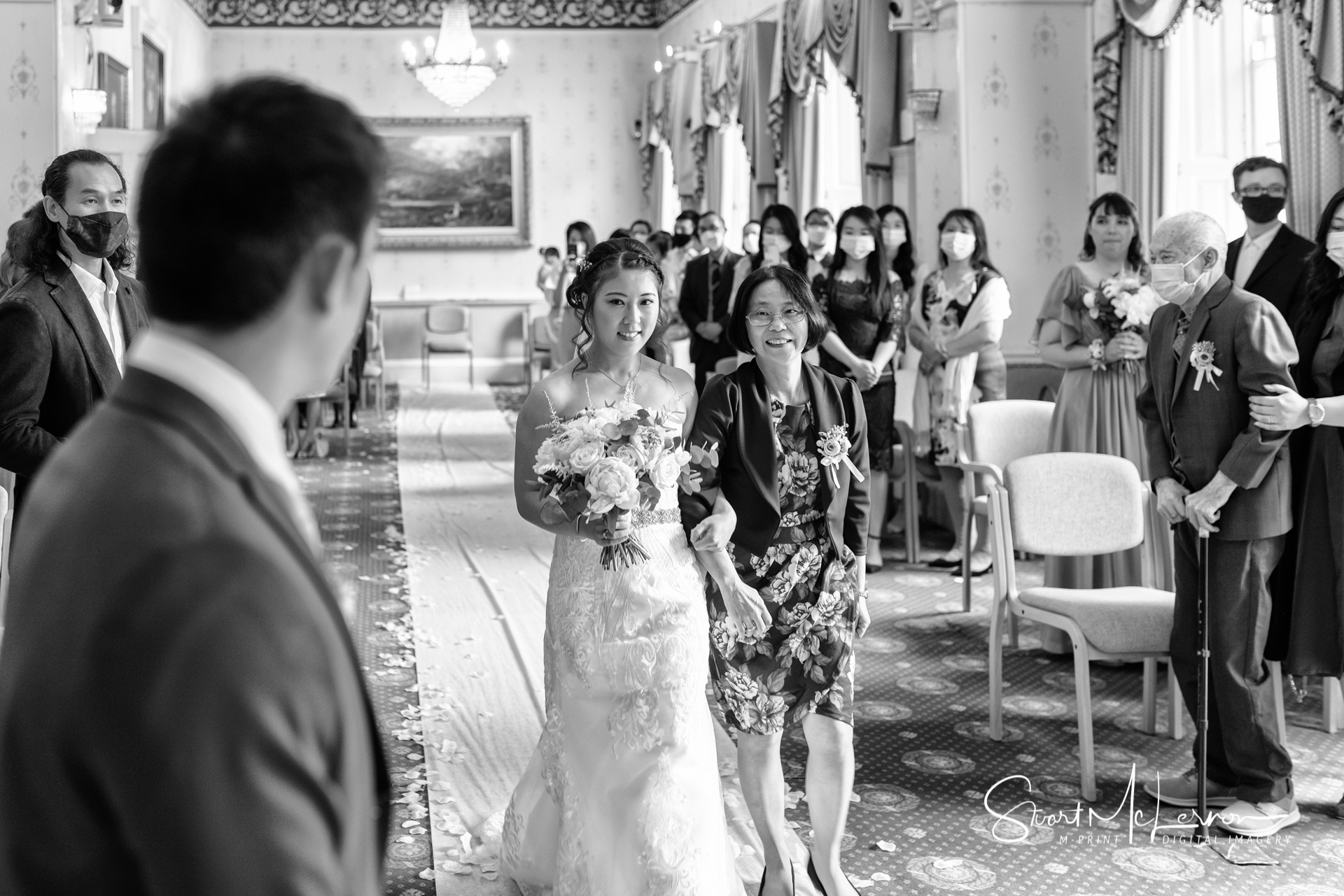 The groom watches his bride being led up the aisle by her mother at Warrington Town Hall